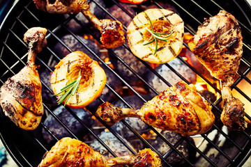 Marinated chicken drumsticks grilling over a BBQ
