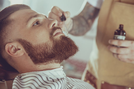 The barber applies the beard oil with a dropper. Photo in vintage style