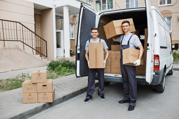 Two young handsome smiling workers wearing uniforms are standing in front of the van full of boxes holding boxes in their hands. House move, mover service.