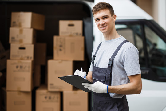 A young handsome smiling worker wearing uniform is standing next to the van full of boxes holding a clipboard in his hands. House move, mover service.