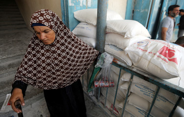 Palestinian woman walks out of an aid distribution center run by UNRWA, in Khan Younis in the southern Gaza Strip