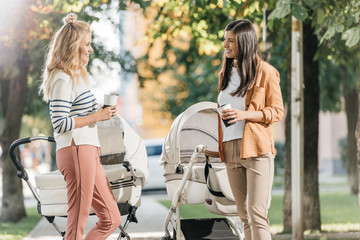 mothers talking, standing with coffee to go and baby strollers in park