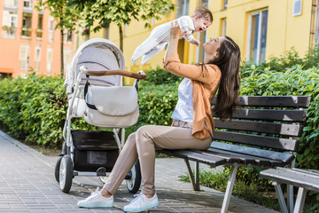 side view of mother holding happy baby on bench near stroller