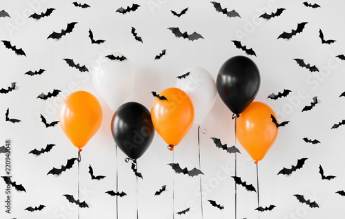 holidays, decoration and party concept - orange, black and white air balloons for halloween with black flying bats on white background