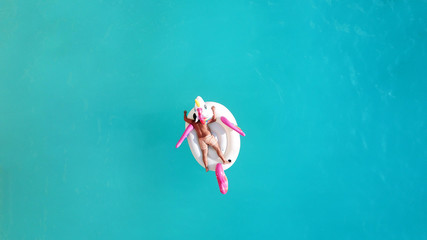 Aerial drone top photo of unidentified man sitting in inflatable unicorn in tropical paradise beach resembling a pool