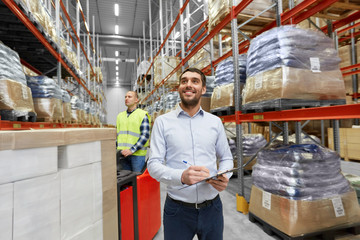 logistic business, shipment and people concept - happy businessman with clipboard and worker loading goods by forklift at warehouse