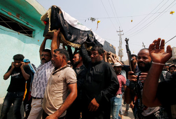 Mourners carry the coffin of a protester, who was killed in clashes with security forces in Basra