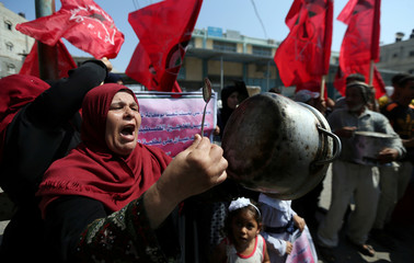 Palestinian woman holds a cooking pot during a protest against a U.S. decision to cut funding to UNRWA, outside an aid distribution center, in Khan Younis in the southern Gaza Strip
