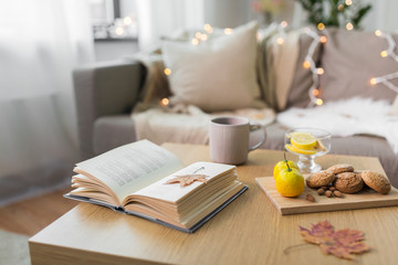 hygge and cozy home concept - book, autumn leaves, cup of tea with lemon, almond nuts and oatmeal cookies on table