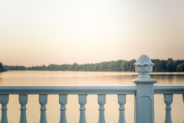 white classic fence frame in evening sunset time on river shore waterfront district for walking with soft colors and empty copy space for your text