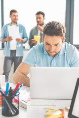 concentrated young businessman using laptop while colleagues standing behind in office