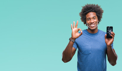 Afro american man holding broken smartphone over isolated background doing ok sign with fingers, excellent symbol