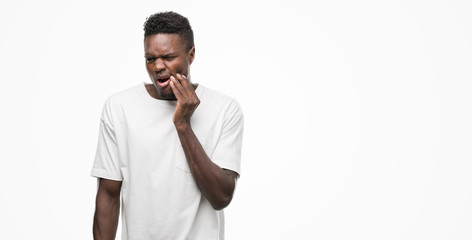Young african american man wearing white t-shirt touching mouth with hand with painful expression because of toothache or dental illness on teeth. Dentist concept.