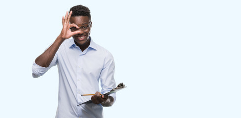 Young african american man holding a clipboarad with happy face smiling doing ok sign with hand on eye looking through fingers