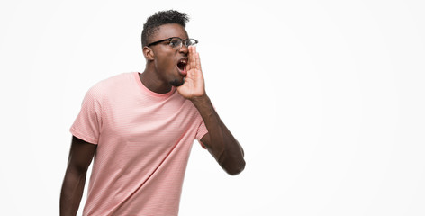 Young african american man wearing pink t-shirt shouting and screaming loud to side with hand on mouth. Communication concept.