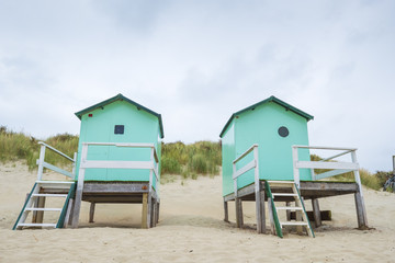 two small beach houses with steps on a sandy beach against the dunes with dune grass