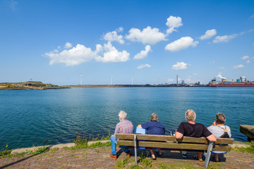 Retired people look across the water on the North Sea coast to modern wind turbines and steel works.