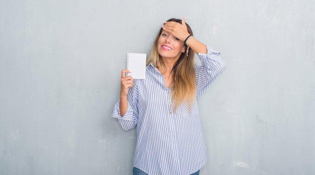 Young adult woman over grey grunge wall holding blank notebook stressed with hand on head, shocked with shame and surprise face, angry and frustrated. Fear and upset for mistake.