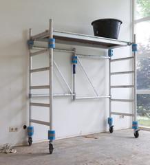 Worker tools - Bucket standing on rolling scaffolding