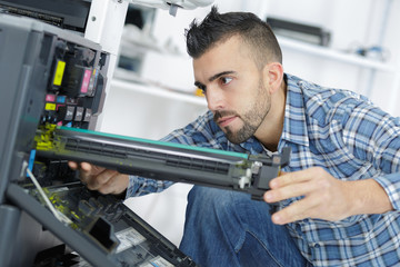 young man repairing printer in modern office