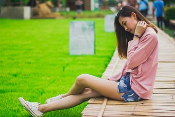 Woman wearing a pink shirt sitting on a bamboo bridge.
