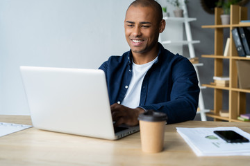 Image of african american businessman working on his laptop. Handsome young man at his desk