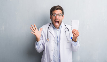 Handsome young doctor man over grey grunge wall holding blank notebook very happy and excited, winner expression celebrating victory screaming with big smile and raised hands