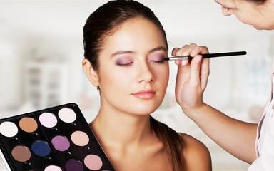Make-up artist making stylish make up to pretty woman Wall mural