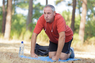 Middle aged man exercising on mat outdoors