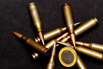 Rifle ammo and one euro coin on black background. Symbolizes the war for money and one of the world's problems.