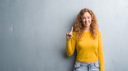 Young redhead woman over grey grunge wall showing and pointing up with finger number one while smiling confident and happy. Wall mural