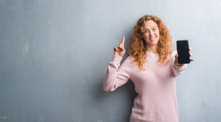 Young redhead woman over grey grunge wall showing smartphone screen surprised with an idea or question pointing finger with happy face, number one