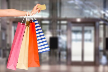 Woman with shopping bags and card on mall background