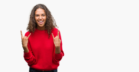 Young hispanic woman wearing red sweater shouting with crazy expression doing rock symbol with hands up. Music star. Heavy concept.