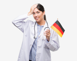 Young hispanic doctor woman holding flag of germany stressed with hand on head, shocked with shame and surprise face, angry and frustrated. Fear and upset for mistake.