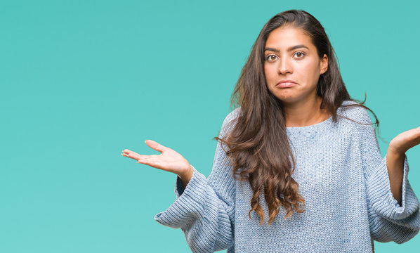 Young beautiful arab woman wearing winter sweater over isolated background clueless and confused expression with arms and hands raised. Doubt concept.