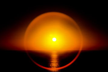 Sunny sunset at the sea. The horizon of the sea. Round glare around the sun at sunset in the sea.