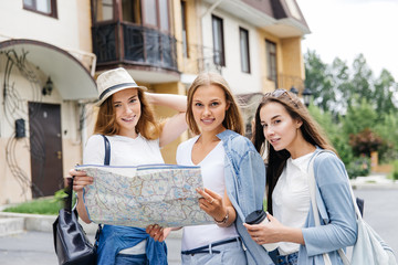 Beautiful woman traveler holding location map in hands in a city