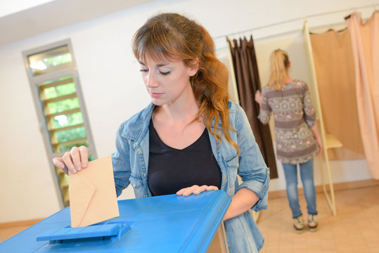 female casting vote at election with ballot paper at box