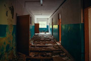 Dark creepy corridor with doors and broken floor in old scary abandoned building, tunnel view
