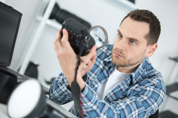 Man looking at camera body with magnifying glass
