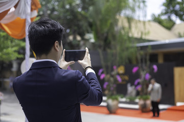 back view of Young Businessman Taking Photos at outdoors event with Mobile.
