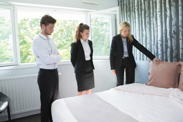 manager showing maid to tidy up bed in hotel room