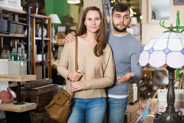 Loving couple in shop of secondhand furniture