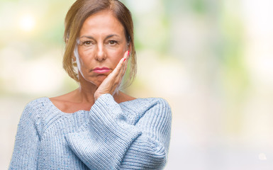 Middle age senior hispanic woman wearing winter sweater over isolated background thinking looking tired and bored with depression problems with crossed arms.