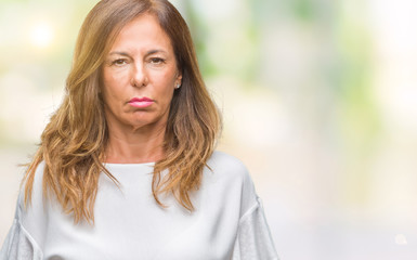 Middle age senior hispanic woman over isolated background with serious expression on face. Simple and natural looking at the camera.