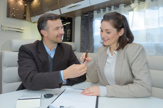 man signing contract while partner is looking at her