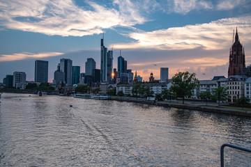 Frankfurter Skyline während des Sonnenuntergangs über dem Main, Blick auf das Bankenviertel, Boot fährt über den Main