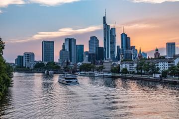 Frankfurter Skyline während des Sonnenuntergangs über dem Main, Blick auf das Bankenviertel - Ein Boot fährt über den Main - Sonnenuntergang mit roten und blauen Pastellfarben