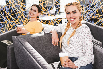 smiling businesswomen with paper cups of coffee at modern coworking office